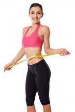 Happy slim woman measuring her waist