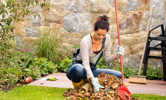 photodune-5582508-young-woman-raking-leaves-autumn-pile-veranda-xs-1