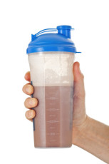 Man's fist holding the post workout chocolate whey protein shake