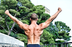 Muscular bodybuilder with hands up for victory