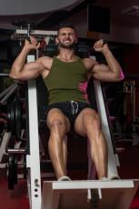 Fit Man Using The Leg Press Machine At A Health Club
