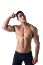 Muscular young man unsure or confused, scratching head