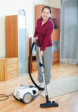 Happy mature woman vacuuming with vacuum cleaner