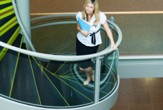 photodune-8213689-businesswoman-walking-up-stairs-in-office-xs