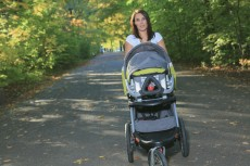 A young woman with a stroller walking in the park
