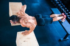 Muscular man doing push ups on fit box