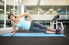 Fit brunette doing pilates on exercise mat at the gym
