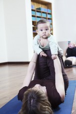 Mother lying on back and holding her baby during a yoga class