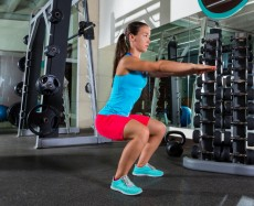 Air squat woman exercise at gym