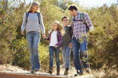 Family Hiking In Countryside Wearing Backpacks