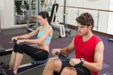 Man and woman working out on the rowing machine at the gym