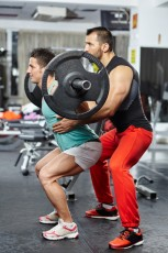Doing barbell squats with personal instructor