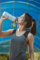 Woman drinking water sweating exercising