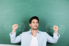 Teacher With Clenched Fists Against Dumbbells Drawn On Chalkboar