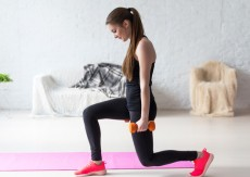 Athletic woman warming up doing weighted lunges with dumbbells workout exercise for butt legs at home healthy lifestyle sport bodybuilding concept