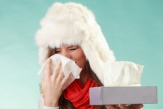 Sick woman sneezing in tissue. Winter cold.