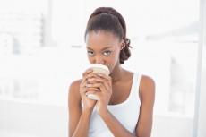 Cute sporty model drinking coffee in bright fitness studio