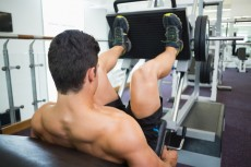 Rear view of male weightlifter doing leg presses in gym