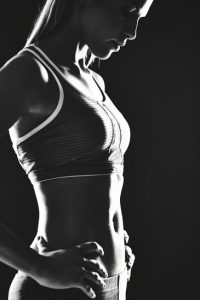 Portrait of slim female in activewear standing in isolation