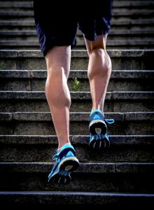 young athletic legs of runner sport man with sharp scarf muscles climbing up city stairs jogging and running in urban training workout our competition in fitness and healthy lifestyle concept