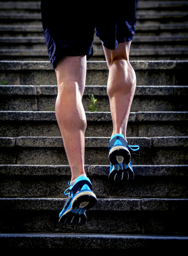 young athletic legs with sharp scarf muscles of runner sport man climbing up city stairs jogging and running in urban training workout