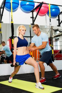 Young woman doing fitness exercises with personal trainer