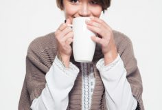 Pretty smiling young woman in knitted jacket drinking tea from big white mug over white background