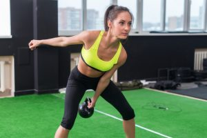 sporty woman doing work-out swinging kettlebell in gym