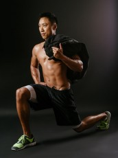 Man doing lunge exercises with sand bag