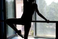 Black silhouette of a ballet dancer in position at the barre near the window