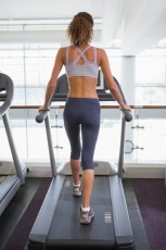 Fit woman walking on the treadmill at the gym