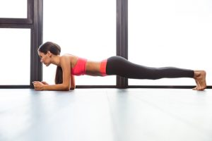 Sports woman doing plank exercise in fitness gym