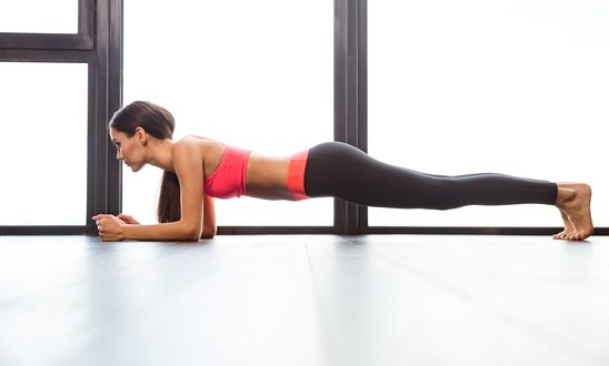 Sports woman doing plank exercise