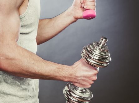 Sporty fit man lifting light and heavy dumbbells weights. Closeup of muscular strong guy training. Bodybuilding exercise.