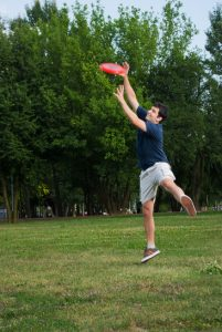 young man catching frisbee outdoors
