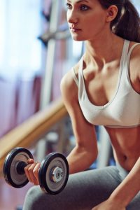 Young woman pumping iron