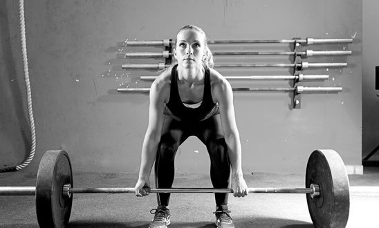 female athlete is preparing to lift deadlift at the crossfit box - focus on the woman