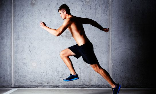 Runner sprinting against concrete wall in garage