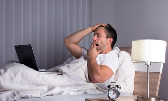 Portrait Of A Sleepy Man Yawning On Bed Looking At Laptop