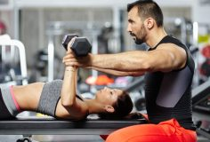 Personal trainer assisting young woman