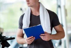 Portrait of a smiling male trainer with clipboard standing in a bright gym