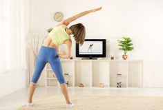 Young woman in sports clothes, photographed from behind, exercise in the room, watching the exercises on TV.