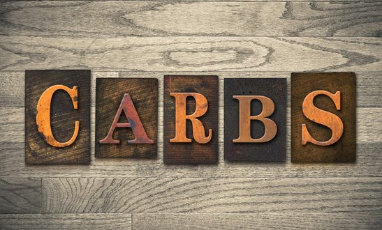 "The word ""CARBS"" theme written in vintage, ink stained, wooden letterpress type on a wood grained background."