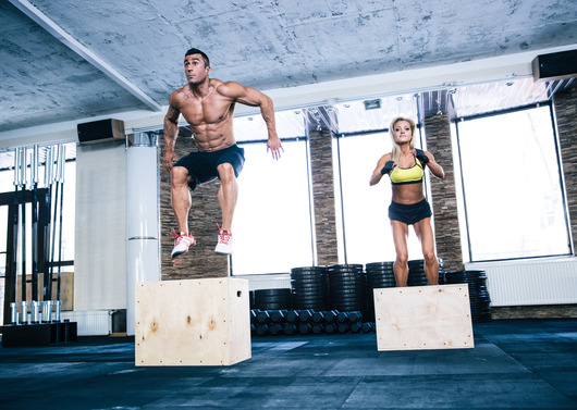 Group of man and woman jumping on fit box