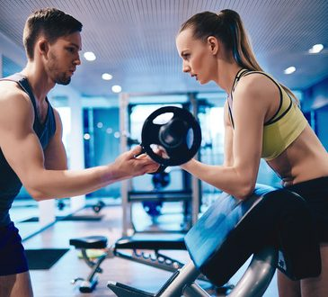 Active woman pumping muscles with trainer helping her