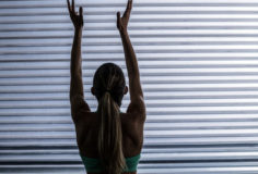 Back view of a muscular woman throwing ball in the air