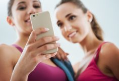 Happy young girls at the gym using a fitness app on a smart phone, technology and training concept