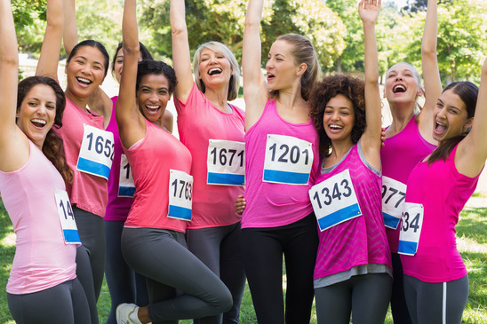 Excited female breast cancer marathon runners cheering in park