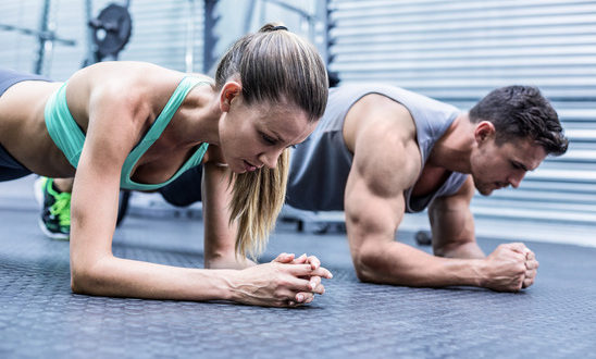 Side view of a muscular couple doing planking exercises
