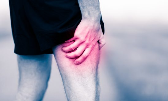 Runners leg pain on workout. Man holding sore and painful leg muscle, sprain or cramp ache filled with red pink bright place. Overtrained injured person when exercising or running outdoors.